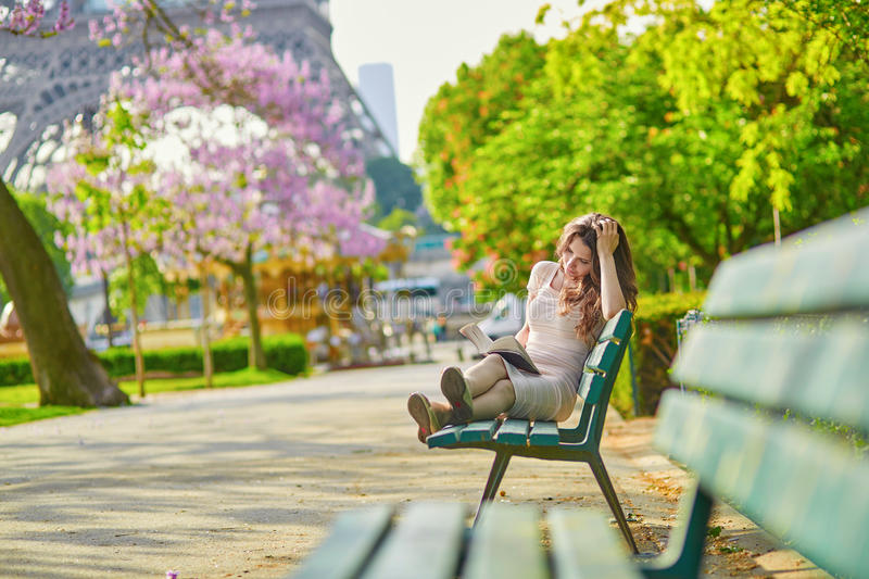 Mujer joven hermosa en la lectura de París en el banco al aire libre imagenes de archivo