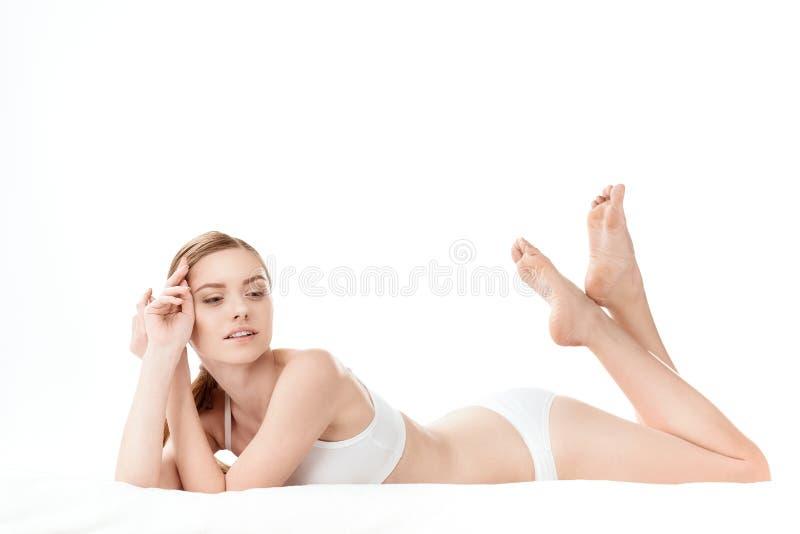 Mujer joven hermosa en la mentira blanca de la ropa interior aislada en blanco fotografía de archivo