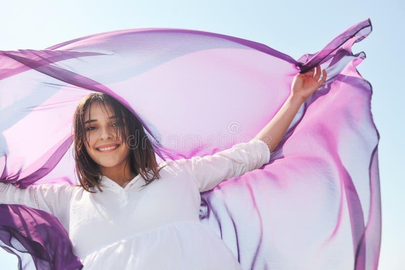 Mujer joven hermosa en la playa con la bufanda foto de archivo