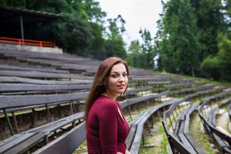 Mujer joven hermosa en la sonrisa al aire libre del teatro foto de archivo