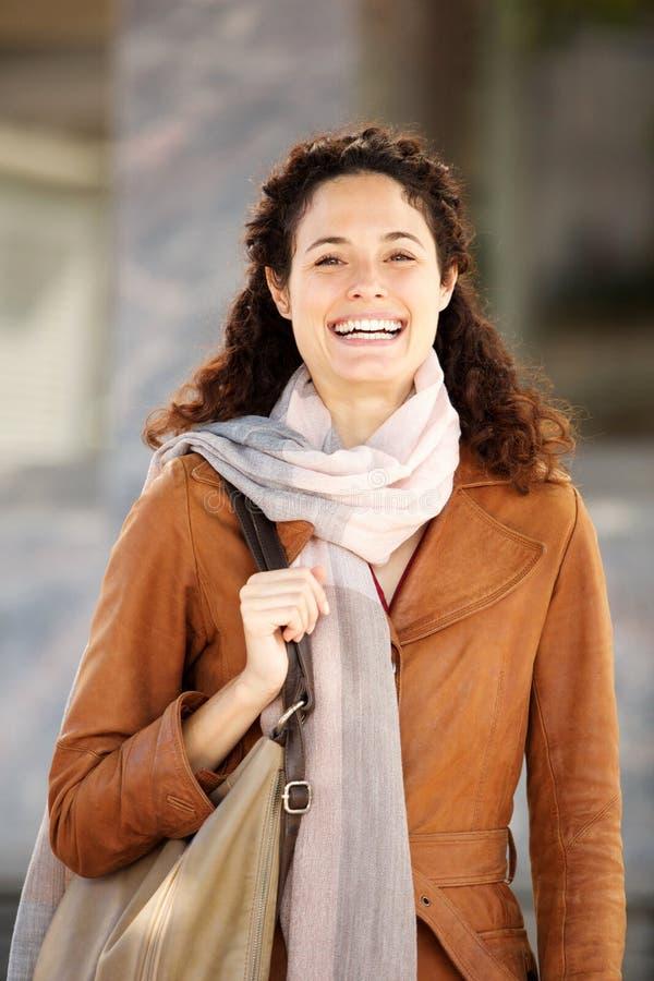 Mujer joven hermosa en la sonrisa de la capa y de la bufanda imagenes de archivo