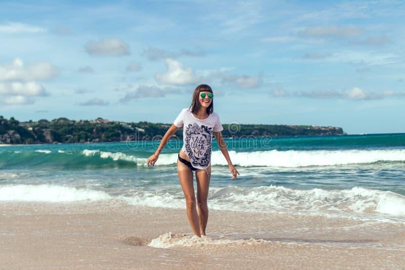 Mujer joven hermosa en las gafas de sol que presentan en la playa de una isla tropical de Bali, Indonesia fotografía de archivo