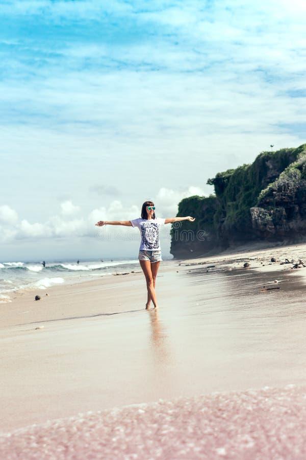 Mujer joven hermosa en las gafas de sol que presentan en la playa de una isla tropical de Bali, Indonesia imagenes de archivo