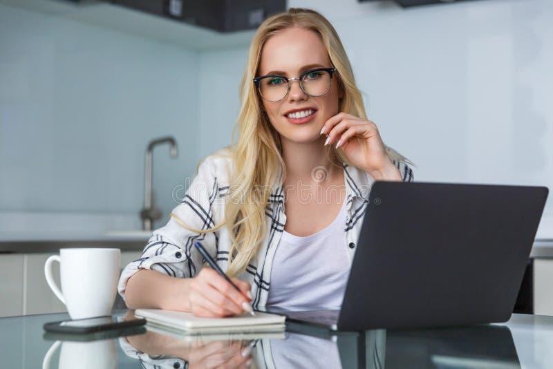 mujer joven hermosa en lentes que sonríe en la cámara mientras que usando el ordenador portátil y que toma notas foto de archivo libre de regalías