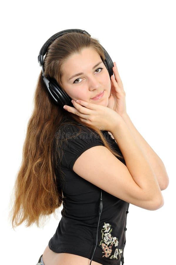 Mujer joven hermosa en los auriculares, sonriendo foto de archivo libre de regalías
