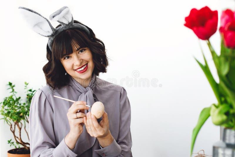 Mujer joven hermosa en los oídos del conejito que pintan el huevo de Pascua en la tabla con la pintura y los cepillos, tulipanes  fotografía de archivo libre de regalías