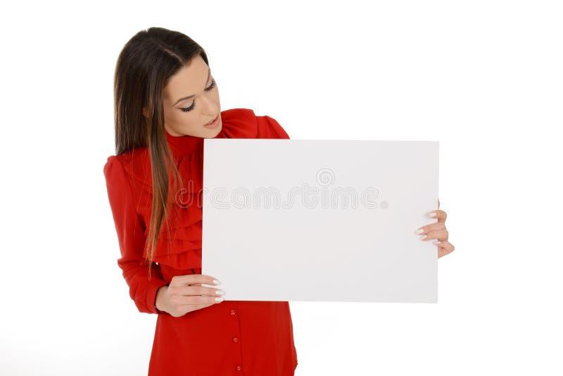 Mujer joven hermosa en los trozos de papel vacíos de la tenencia roja, mirando en el papel fotos de archivo libres de regalías