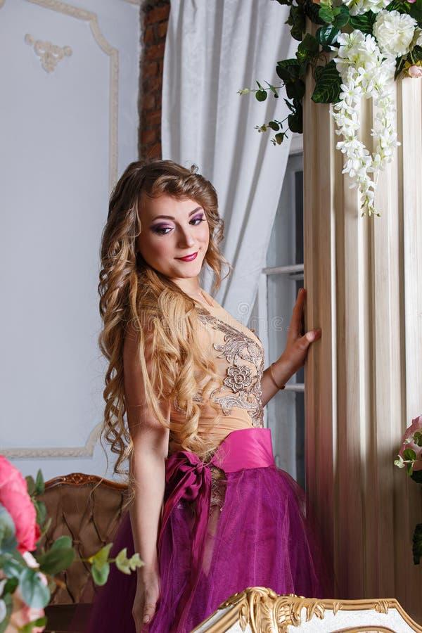 Mujer joven hermosa en los vestidos brillantes que presentan en interior foto de archivo
