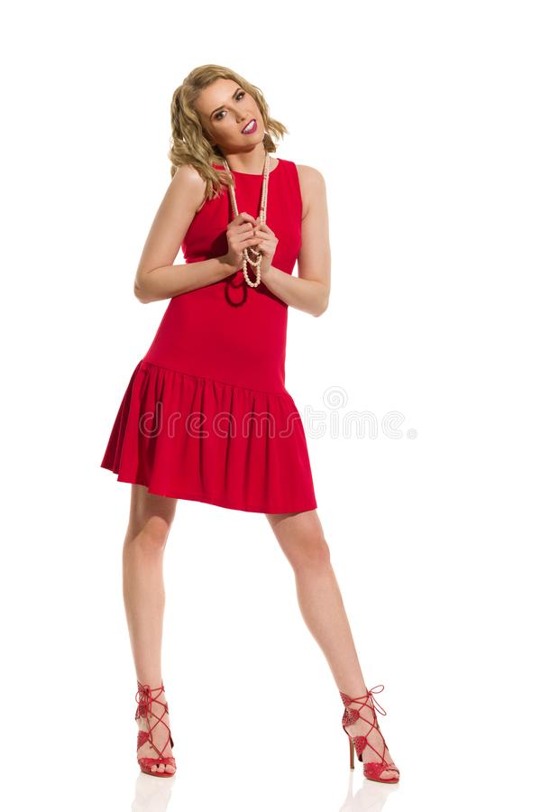 Mujer joven hermosa en Mini Dress, tacones altos y collar rojos de la perla fotografía de archivo libre de regalías