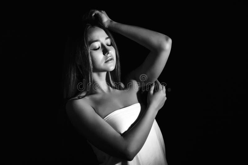 Mujer joven hermosa en oscuridad imagen de archivo