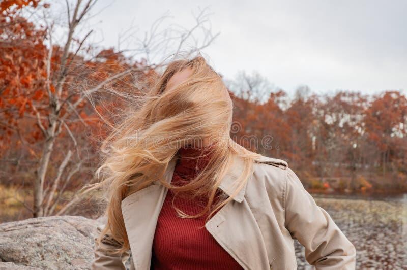 Mujer joven hermosa en parque del otoño Cara ocultada detrás del pelo, pelo que sopla del viento de muchacha hermosa al aire libr fotografía de archivo libre de regalías
