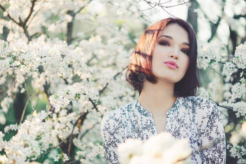 Mujer joven hermosa en Sakura floreciente foto de archivo