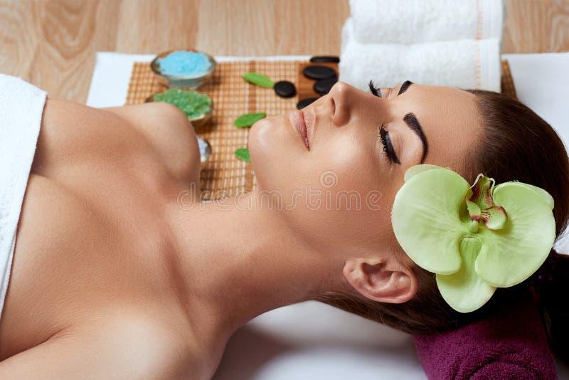 Mujer joven hermosa en sal?n del balneario Hembra del masaje de cara Tratamiento facial cosmetolog?a Cuidado de la carrocer?a fotos de archivo libres de regalías