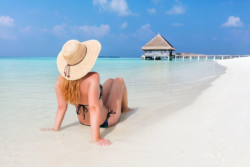 Mujer joven hermosa en sentarse del sunhat relajado en la playa tropical en Maldivas fotos de archivo libres de regalías