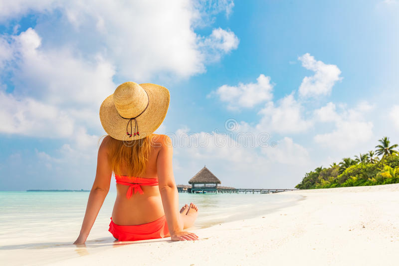 Mujer joven hermosa en sentarse del sunhat relajado en la playa tropical en Maldivas fotos de archivo