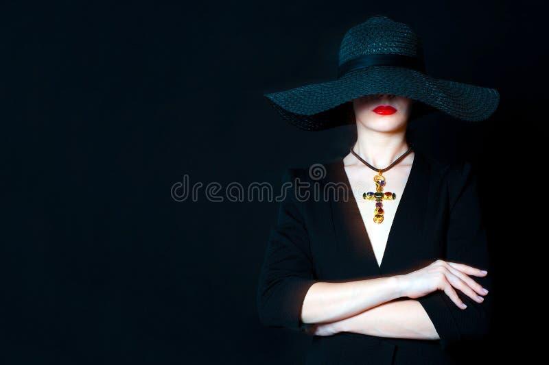 Mujer joven hermosa en sombrero negro con la cruz de la joya imagen de archivo libre de regalías