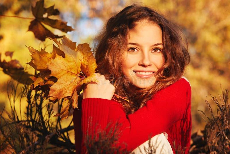 Mujer joven hermosa en suéter en parque del otoño foto de archivo