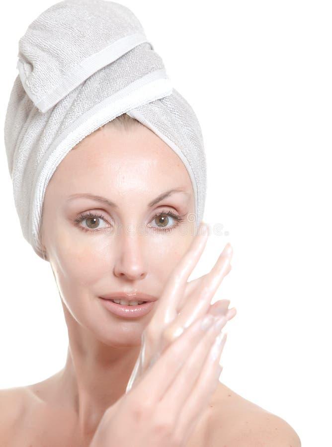Mujer joven hermosa en toalla con una crema cosmética imagen de archivo