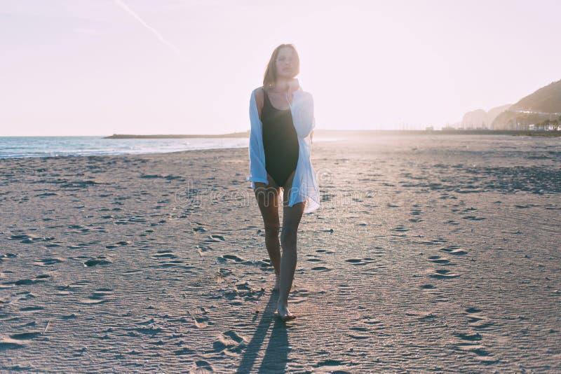 Mujer joven hermosa en traje de baño en la playa imagen de archivo