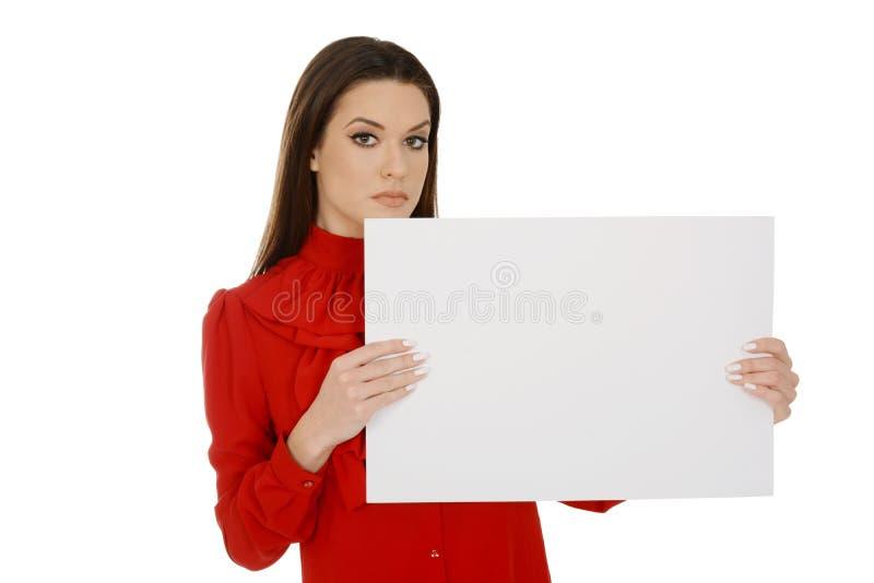 Mujer joven hermosa en trozos de papel vacíos de la tenencia roja fotografía de archivo