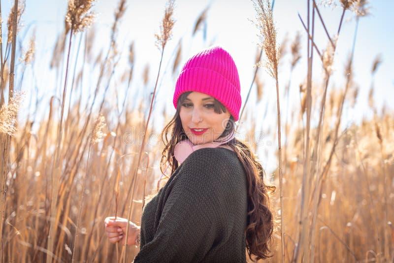 Mujer joven hermosa en un campo de la m?sica que escucha de la alta hierba fotos de archivo libres de regalías