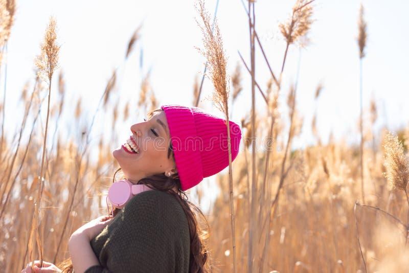 Mujer joven hermosa en un campo de la m?sica que escucha de la alta hierba imagenes de archivo