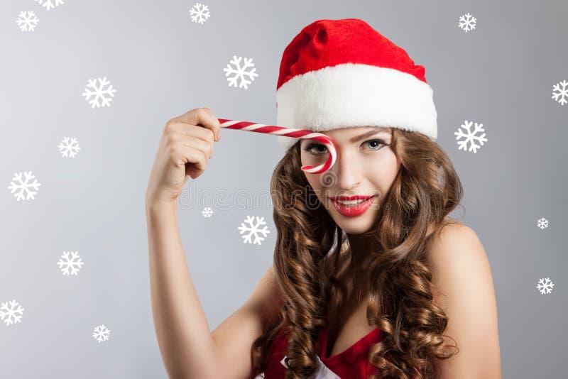 Mujer joven hermosa en un sombrero de Santa Claus Retrato de la Navidad de una muchacha con un caramelo del regaliz foto de archivo
