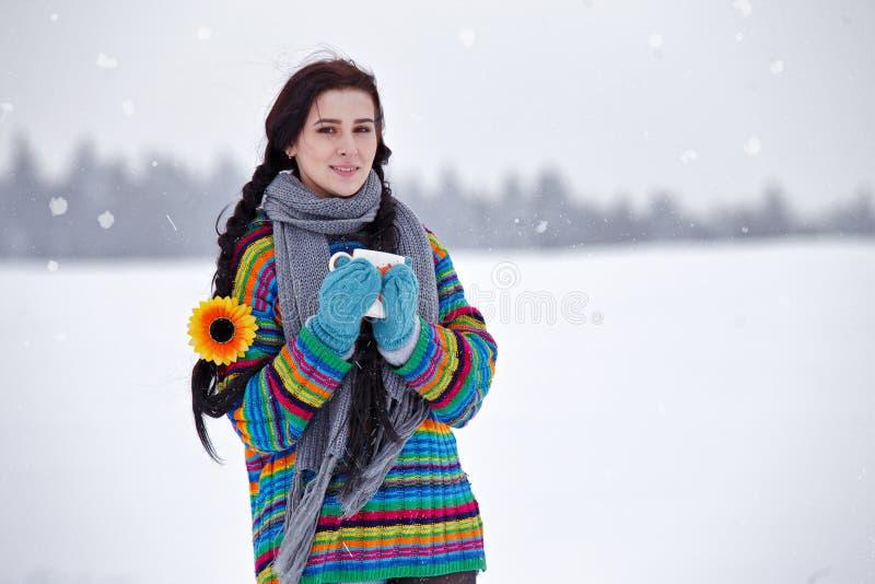 Mujer joven hermosa en un suéter en un paseo del invierno con una taza o foto de archivo