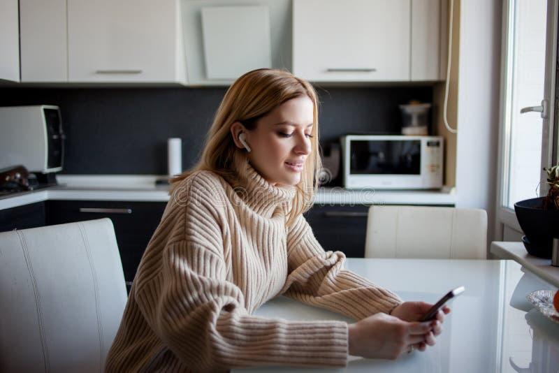 Mujer joven hermosa en un su?ter acogedor que se sienta en la cocina y que escucha la m?sica usando los auriculares inal?mbricos fotos de archivo