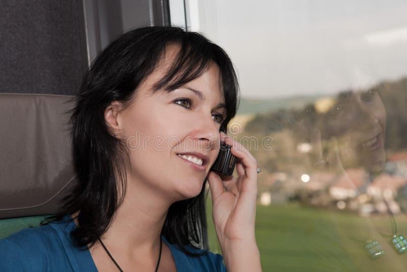 Mujer joven hermosa en un teléfono sonriente del tren imagenes de archivo