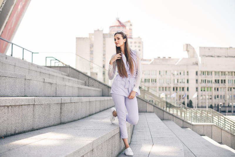 Mujer joven hermosa en un traje púrpura del negocio contra un fondo de la ciudad imagen de archivo libre de regalías