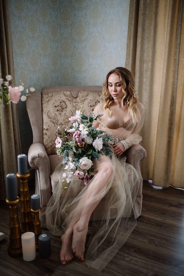Mujer joven hermosa en un vestido de la casa en el gabinete de señora, adornado con las flores hermosas, sentándose en una cama b imagen de archivo