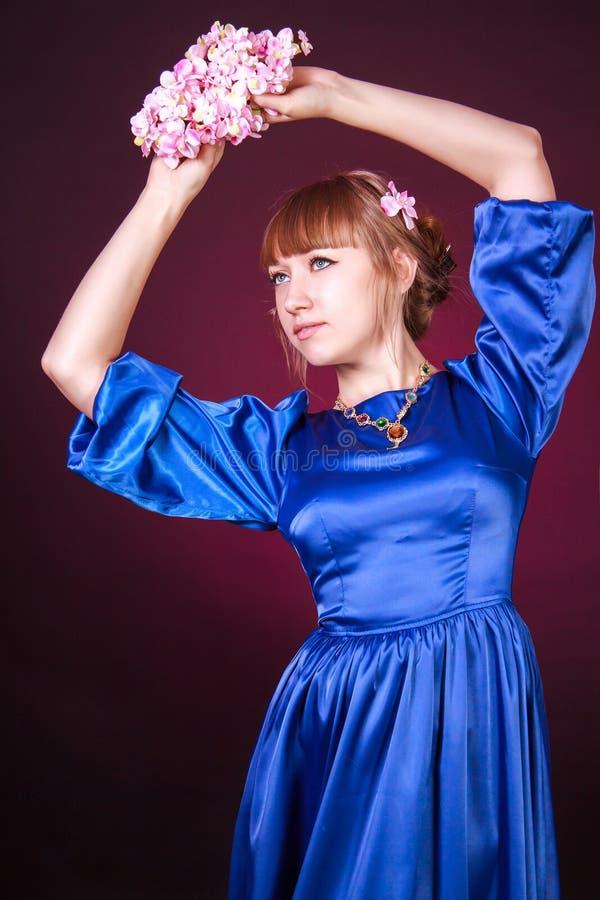 Mujer joven hermosa en un vestido de noche azul imagen de archivo