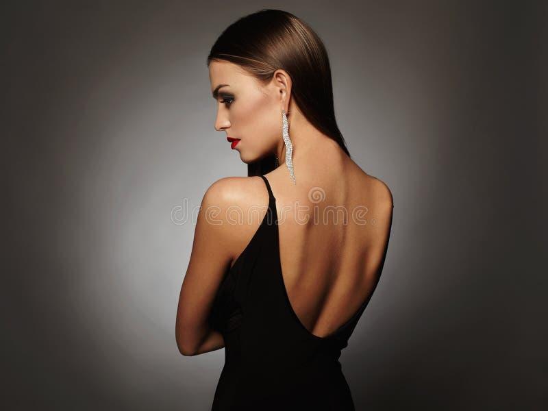 Mujer joven hermosa en un vestido sexy negro que presenta en el estudio, lujo muchacha de la morenita de la belleza foto de archivo