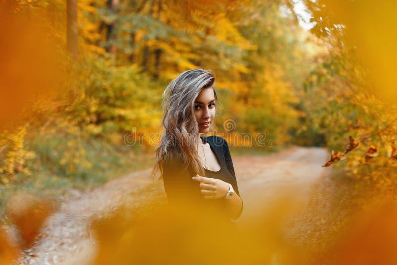 Mujer joven hermosa en una camisa negra en el parque en día del otoño fotografía de archivo libre de regalías