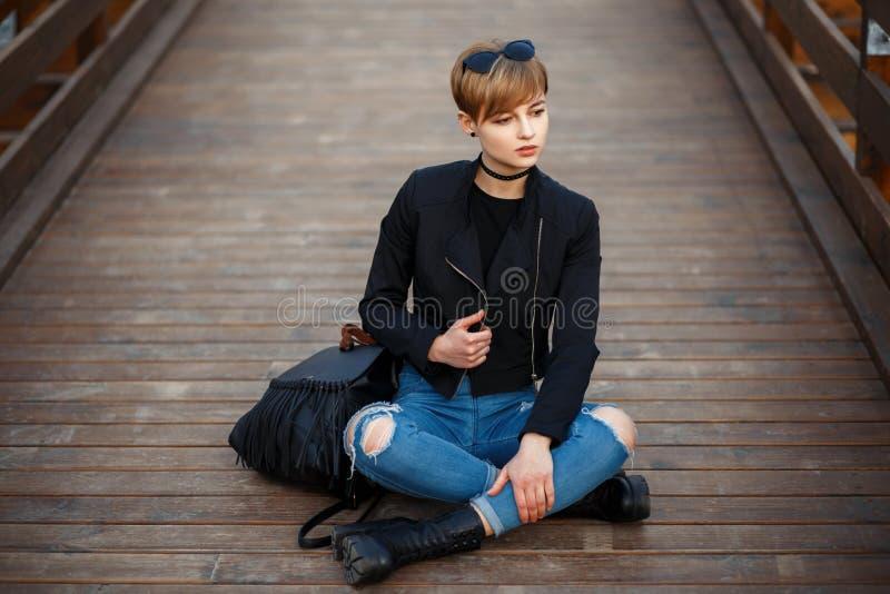 Mujer joven hermosa en una chaqueta negra de moda, tejanos fotografía de archivo
