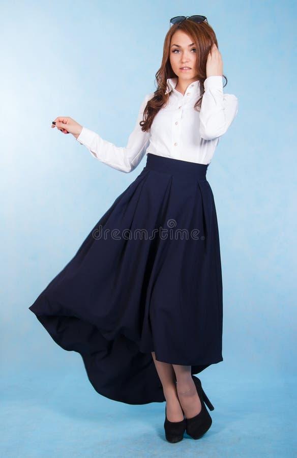 Mujer joven hermosa en una falda azul larga fotografía de archivo libre de regalías