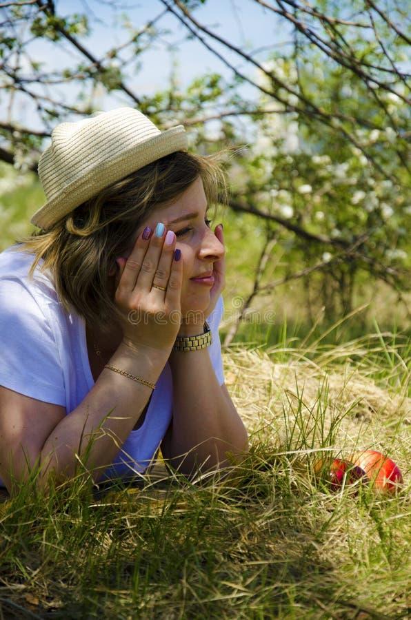 Mujer joven hermosa en una pelusa, mintiendo en el campo, la hierba verde, las manzanas y las flores Al aire libre disfrute de la fotografía de archivo
