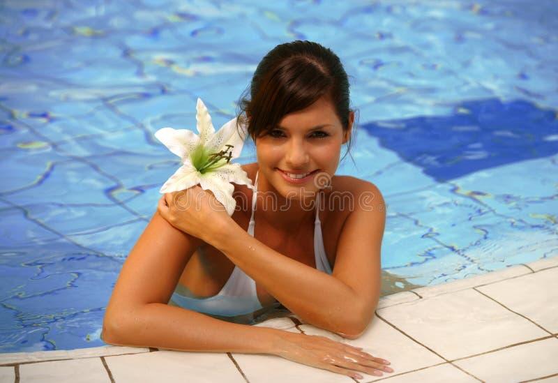 Mujer joven hermosa en una piscina imagenes de archivo
