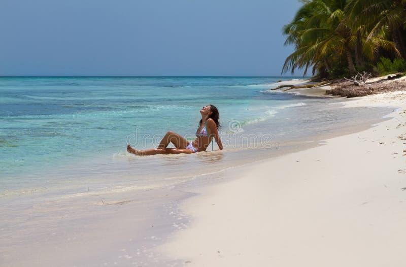 Mujer joven hermosa en una playa tropical imagenes de archivo