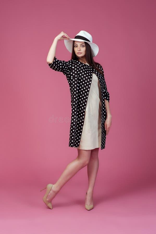 Mujer joven hermosa en vestido, chaqueta del lunar y sombrero beige elegantes del verano Muchacha que presenta en un fondo rosado foto de archivo libre de regalías