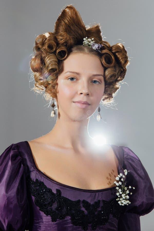 Mujer joven hermosa en vestido del vintage con el pelo del diseñador Bola, igualando a la recepción fotografía de archivo libre de regalías