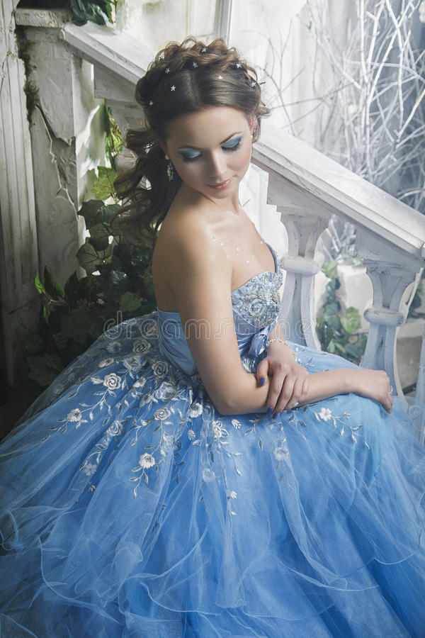 Mujer joven hermosa en vestido largo azul magnífico como Cenicienta con estilo perfecto del maquillaje y de pelo foto de archivo libre de regalías