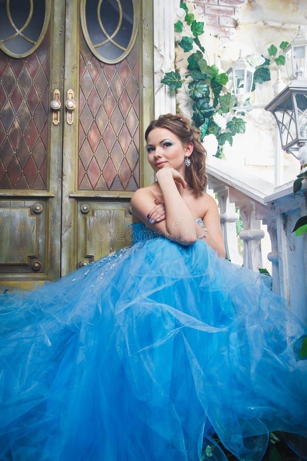 Mujer joven hermosa en vestido largo azul magnífico como Cenicienta con estilo perfecto del maquillaje y de pelo imagen de archivo