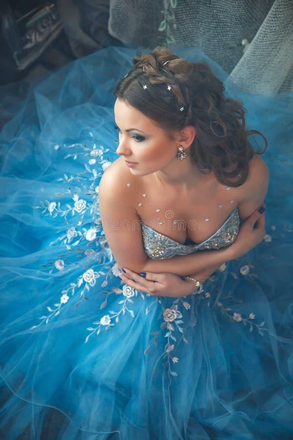 Mujer joven hermosa en vestido largo azul magnífico como Cenicienta con estilo perfecto del maquillaje y de pelo fotos de archivo libres de regalías