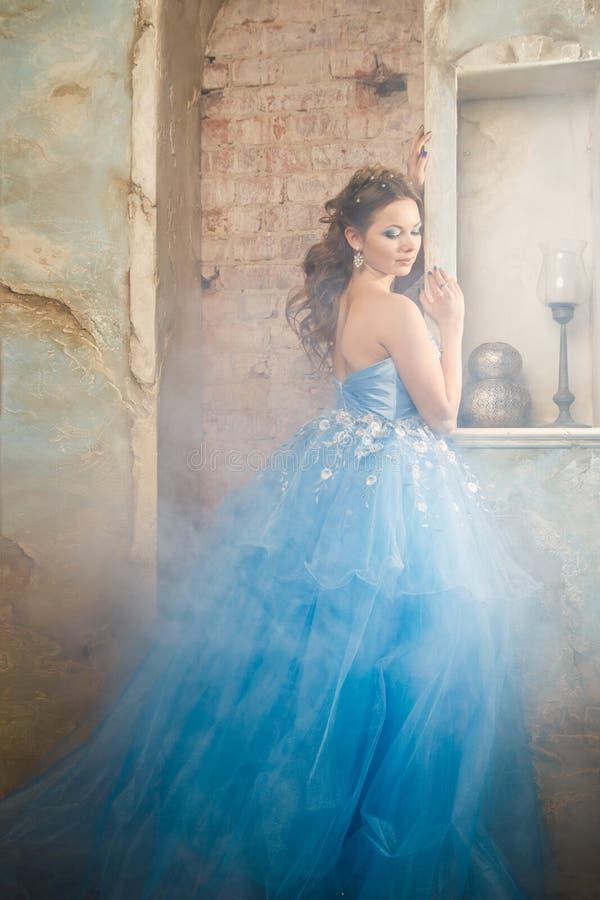 Mujer joven hermosa en vestido largo azul magnífico como Cenicienta con estilo perfecto del maquillaje y de pelo foto de archivo