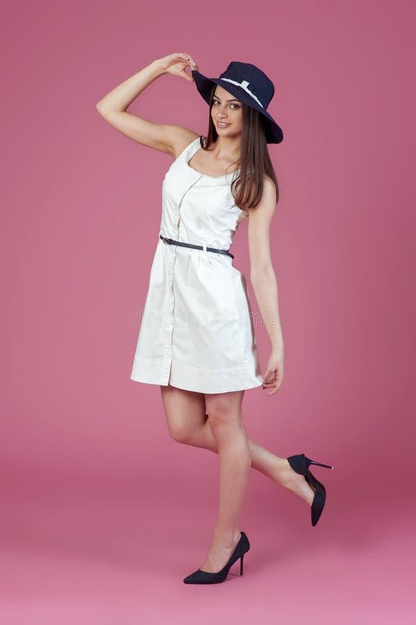 Mujer joven hermosa en vestido y sombrero blancos elegantes del verano Muchacha que presenta en un fondo rosado Foto de la manera fotos de archivo