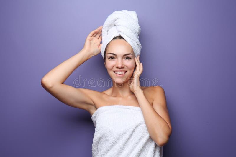 Mujer joven hermosa envuelta en toalla en fondo del color fotografía de archivo libre de regalías