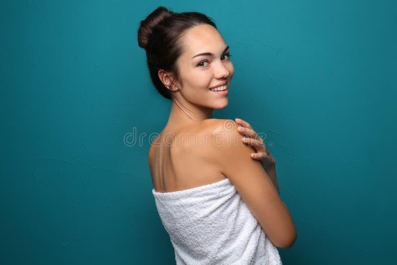 Mujer joven hermosa envuelta en toalla en fondo del color imagenes de archivo