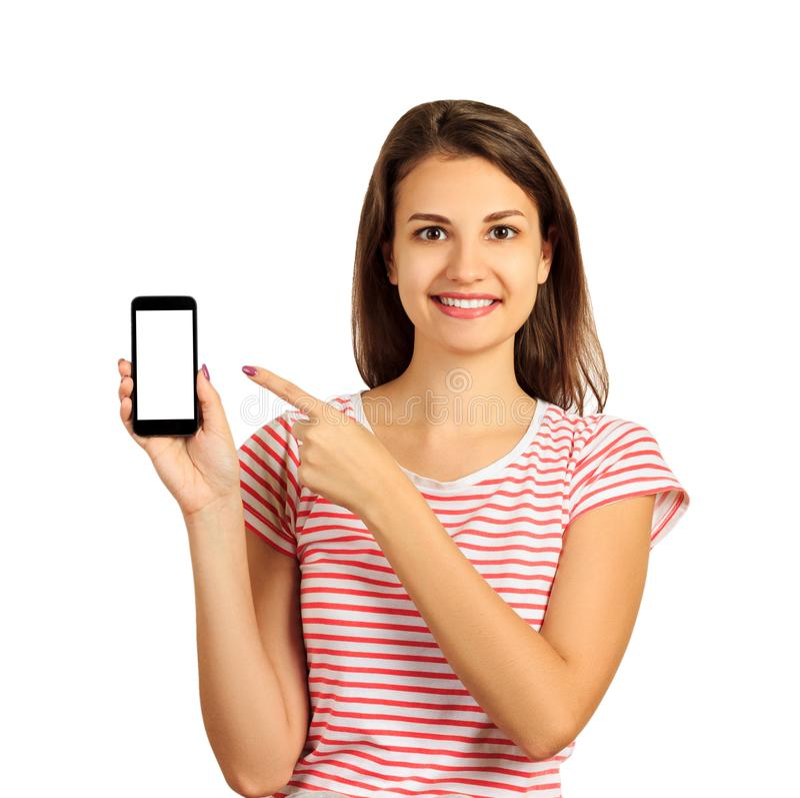 Mujer joven hermosa feliz con el pelo largo que sostiene el teléfono móvil de la pantalla en blanco y que señala el finger muchac fotos de archivo